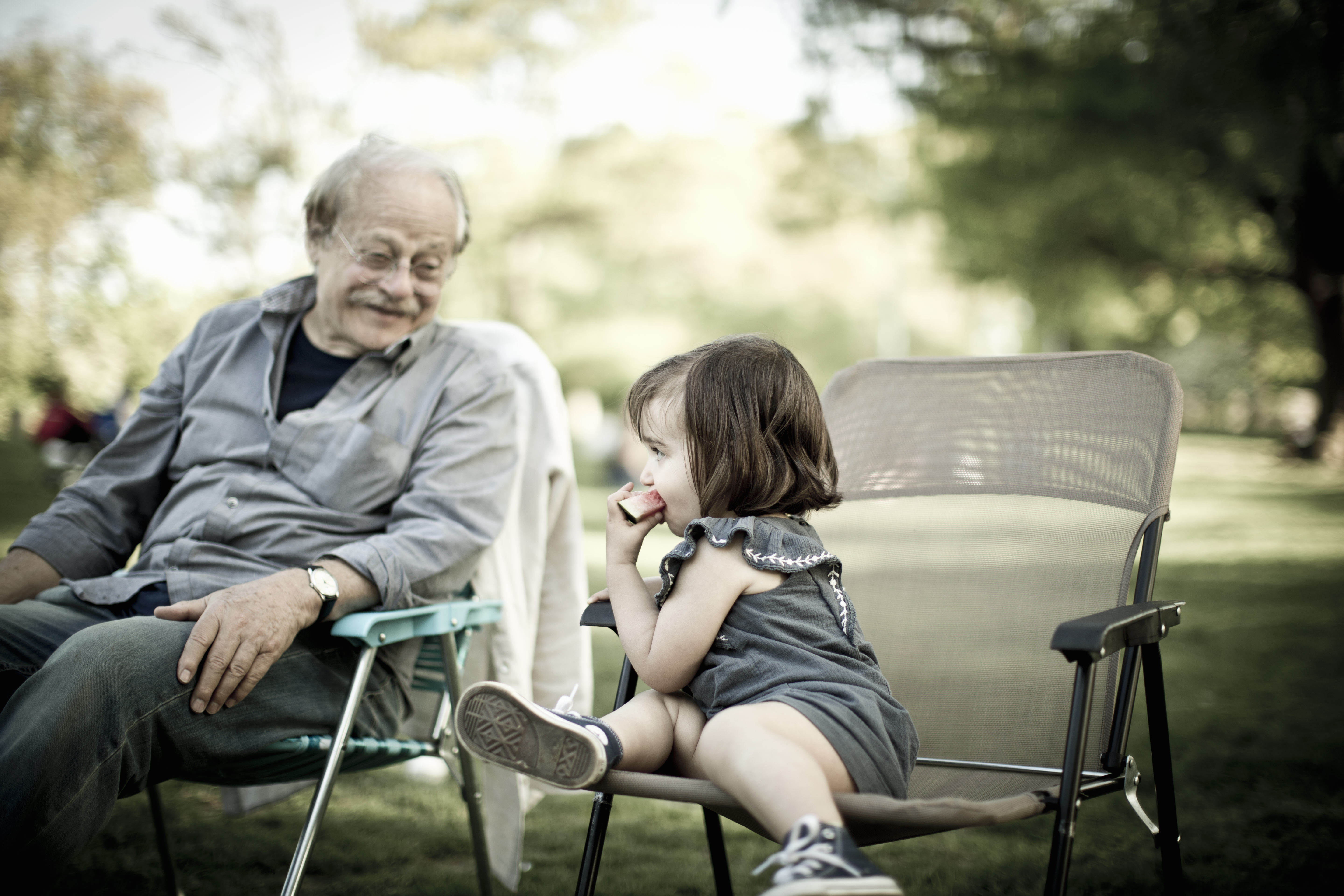 An elderly man sitting with a child at a park.