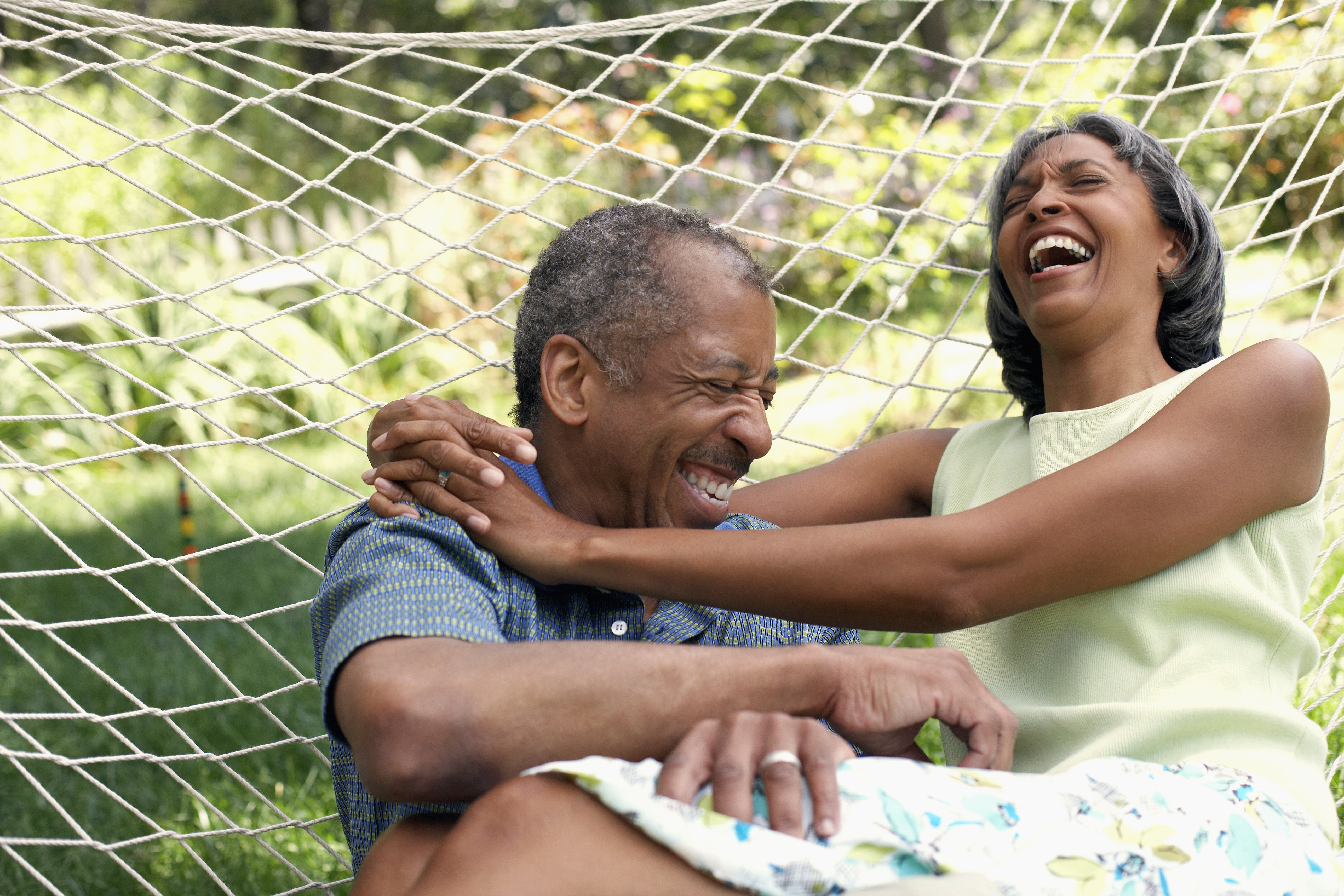 An older couple hugging and laughing in a hammock.